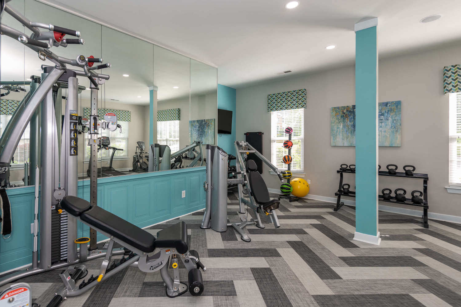 Fitness center with workout machines, free weights, and medicine balls.