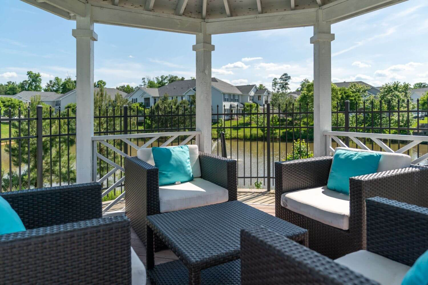 Outdoor pool area seating under a gazebo.