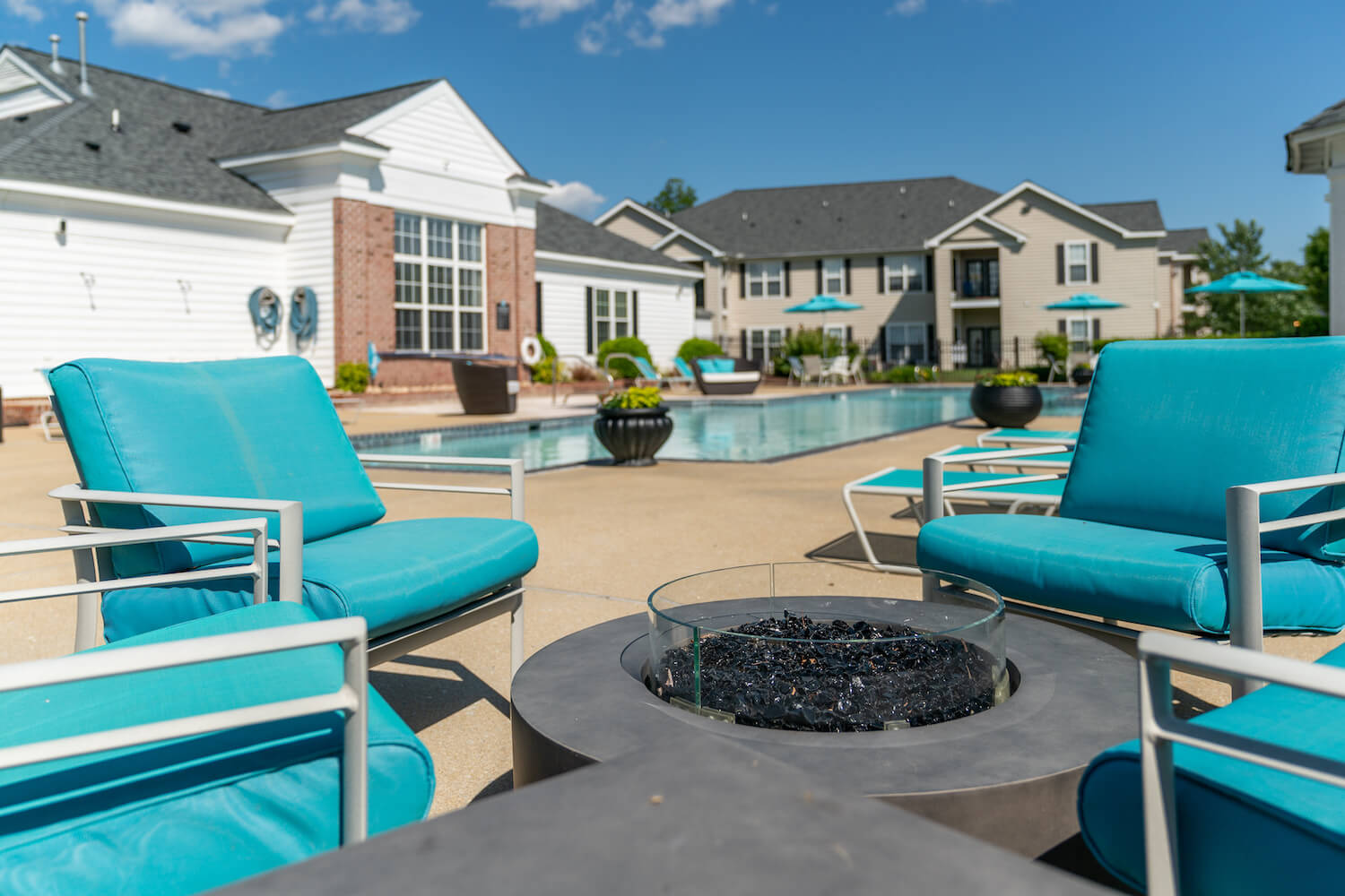 Outdoor pool area lounge seating with modern style fire pit.